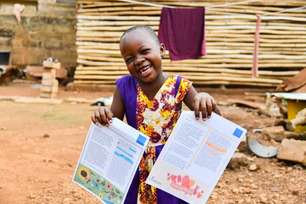 Fortune, a sponsored child in Togo, holds up letters from her sponsor. She is smiling and wearing a colorful dress.