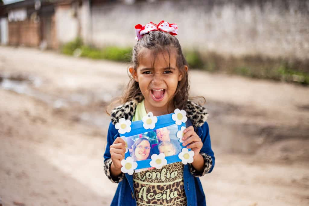 Débora is wearing a yellow shirt with a black pattern on it and a blue jacket. She is standing outside her home and is holding up a picture of her sponsors.
