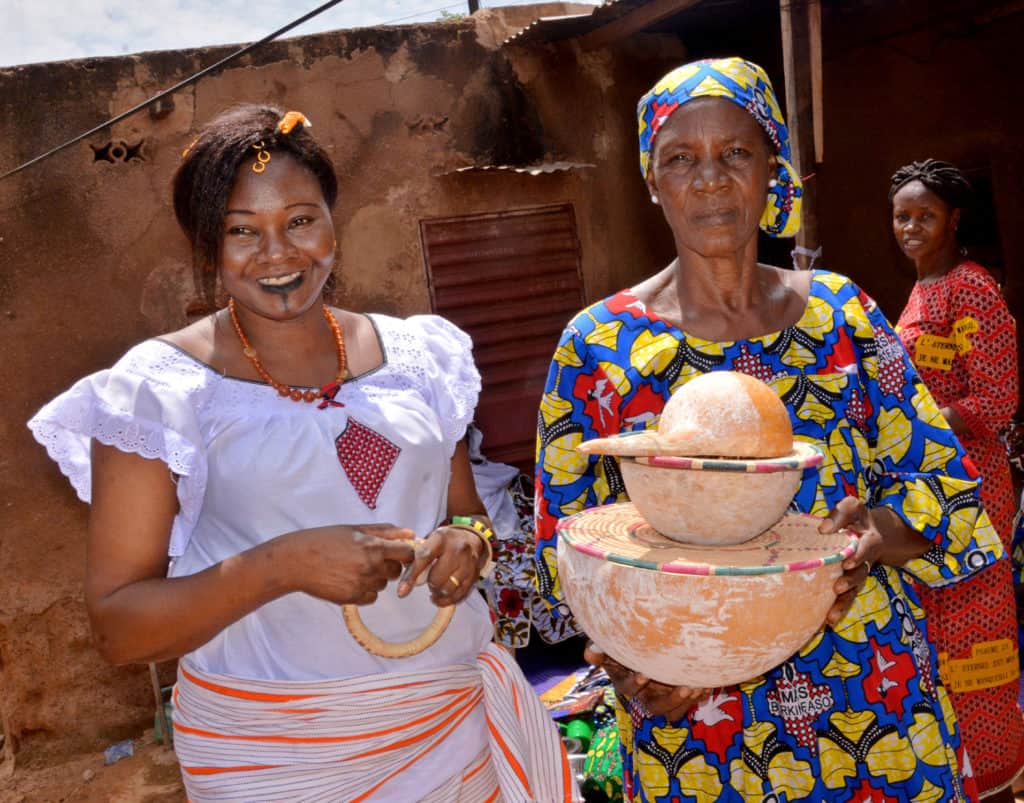 Odette and another woman in Burkina Faso are standing together wearing colorful clothing. One is holding bowls covered with woven lids.
