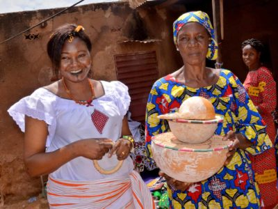 Odette and another woman in Burkina Faso are wearing brightly colored clothing and standing outdoors together. One woman is holding two ceramic bowls