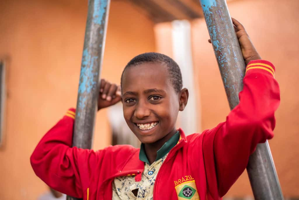 Abel, in a red jacket, is outside the church smiling and holding onto the poles of a piece of playground equipment. The building in the background is orange.