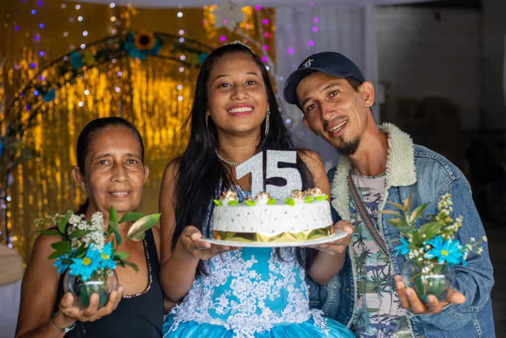Girl wearing a blue dress and is holding a cake with a large 15 on it. She is standing with her father and grandmother in front of a gold curtain.