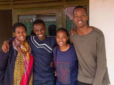 Christian is wearing a navy blue shirt with gray stripes down the center. He is outside his aunt's home with his Aunt Pascasie, and his cousins, Cynthia and Mugisha. They have their arms around each other.