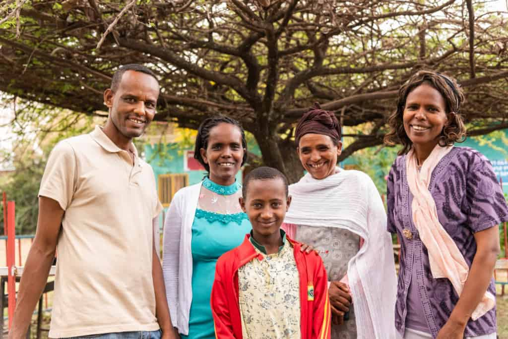 Abel stands with Mr. Abaya (project director), Shahitu (health worker), Astede (Abel's mom) and Meseret (social worker).]