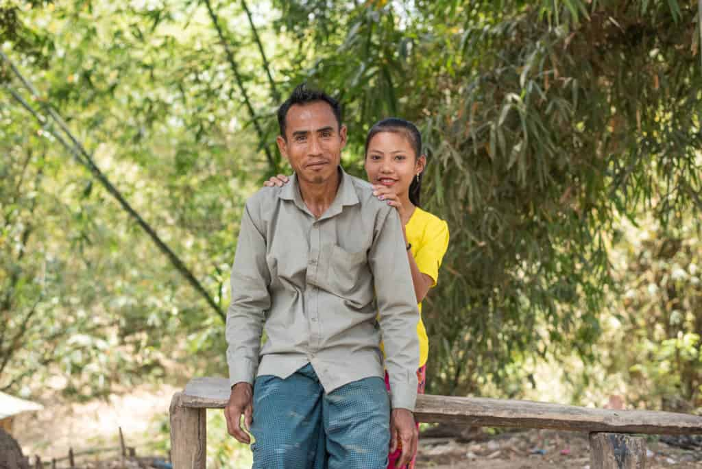 Baby is wearing a yellow shirt and is standing behind her father, who is wearing a tan shirt and blue pants. They are outside and there are bamboo trees in the background.
