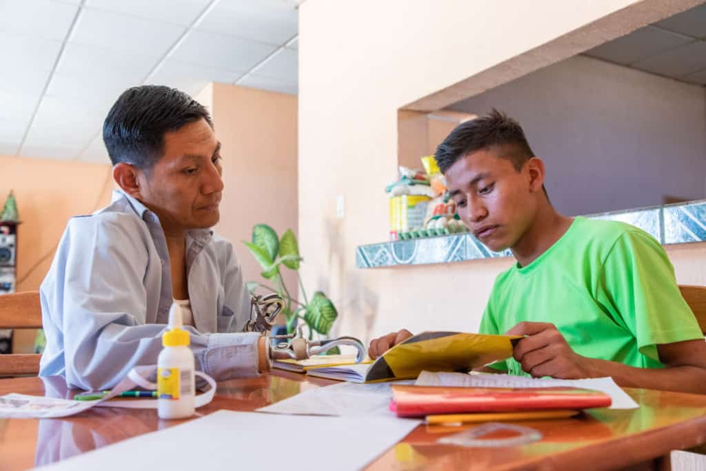 Jose is wearing a bright green shirt and black shorts. His father, Rene, is wearing a light blue shirt and jeans. They are sitting together at a table and Rene is helping Jose with his homework.