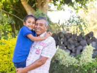 Thatiana is wearing jeans and a dark blue shirt. Her father, Remberto, is wearing a plaid shirt and gray pants. Remberto is holding Thatiana. They are standing outside and there are trees in the background.