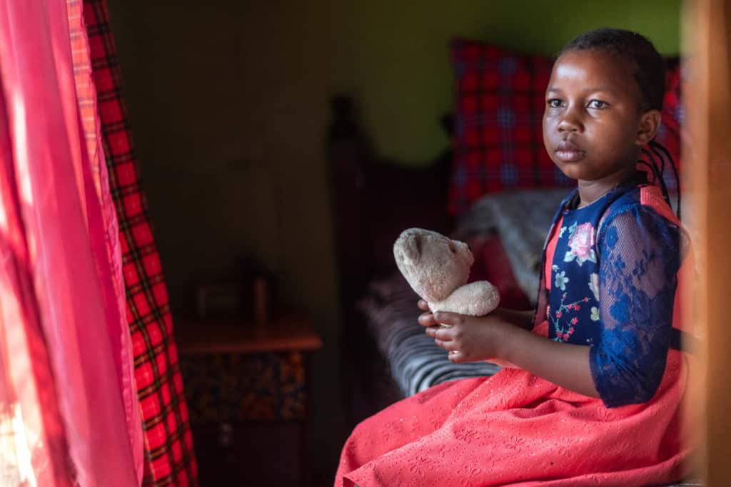 Shaniz is one of Kenya's girls. She is wearing a red dress with a blue floral print jacket. She is sitting on a bed in her home and is holding a teddy bear. There are red curtains in the window.