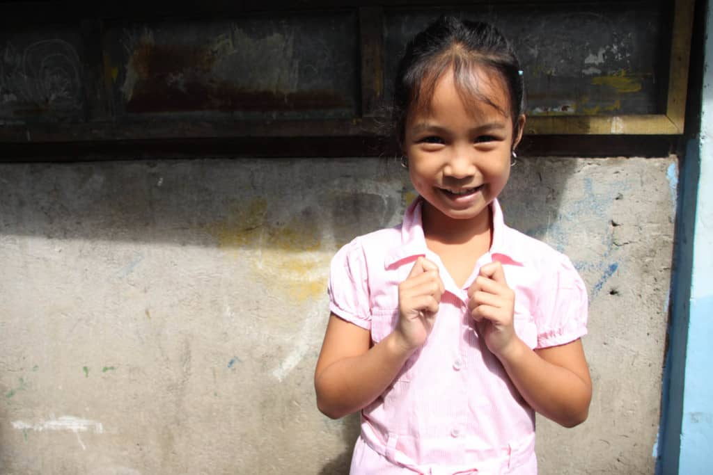 Girl standing outside her home, wearing her light pink dress she got for Christmas last year. She is holding onto the collar of the dress.