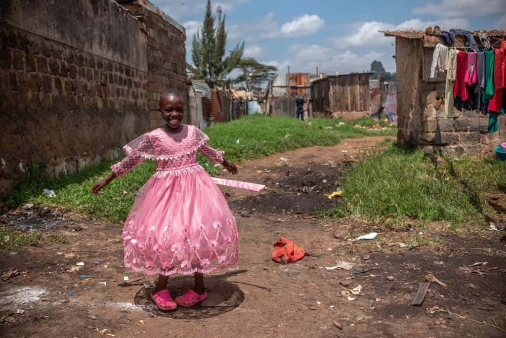 Leach is one of Kenya's girls. She is smiling and looking at the camera as she is wearing her pink dress and shoes.