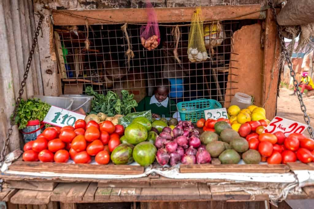 Tracy is pictured here sitting behind a display of fruits at her grandmother's shop.