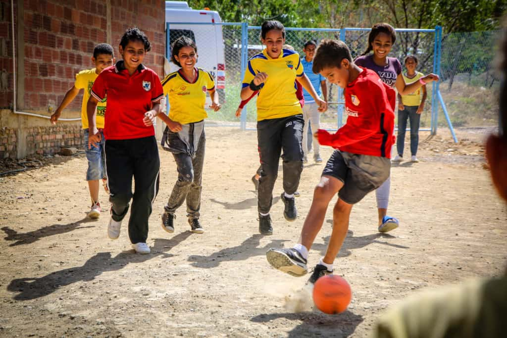 A group of boys and girls are playing soccer on a dirt field at the project. A boy in a red shirt is kicking the ball.
