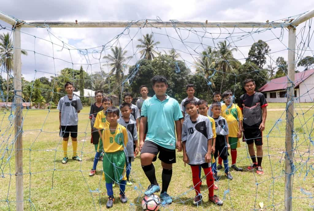 A group of boys standing together behind a ripped soccer goal, net. One is wearing mint t-shirt. Another is wearing black t-shirt on the right side.