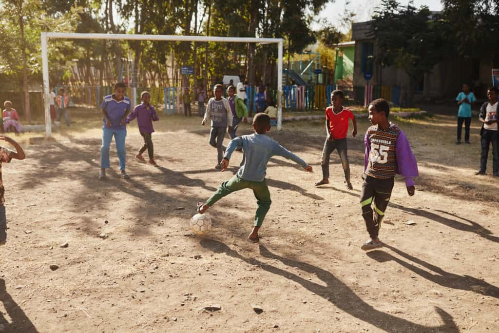A group of boys are playing soccer on the dirt field outside the center. A boy in a blue shirt and green pants has his foot near the ball. There are trees and a white soccer goal in the background.