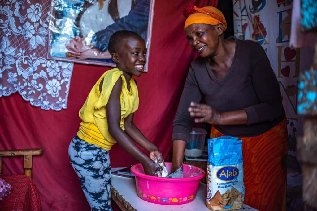 Leach and her grandmother are seen here laughing and smiling and making Chapati, or Indian flatbread.
