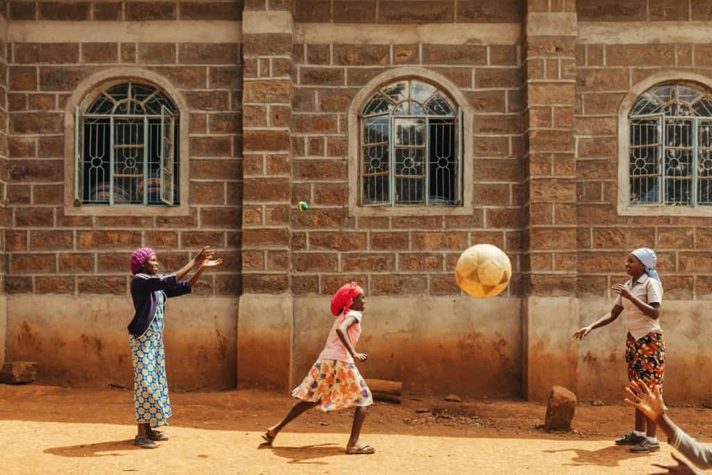 Group portraits and shots of teen girls playing outside project in Solai, Kenya