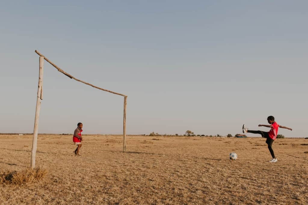 Praise, a 10 year old girl, wearing a red athletic sport shirt, kicks at a soccer ball on the dirt ground playing with another child.