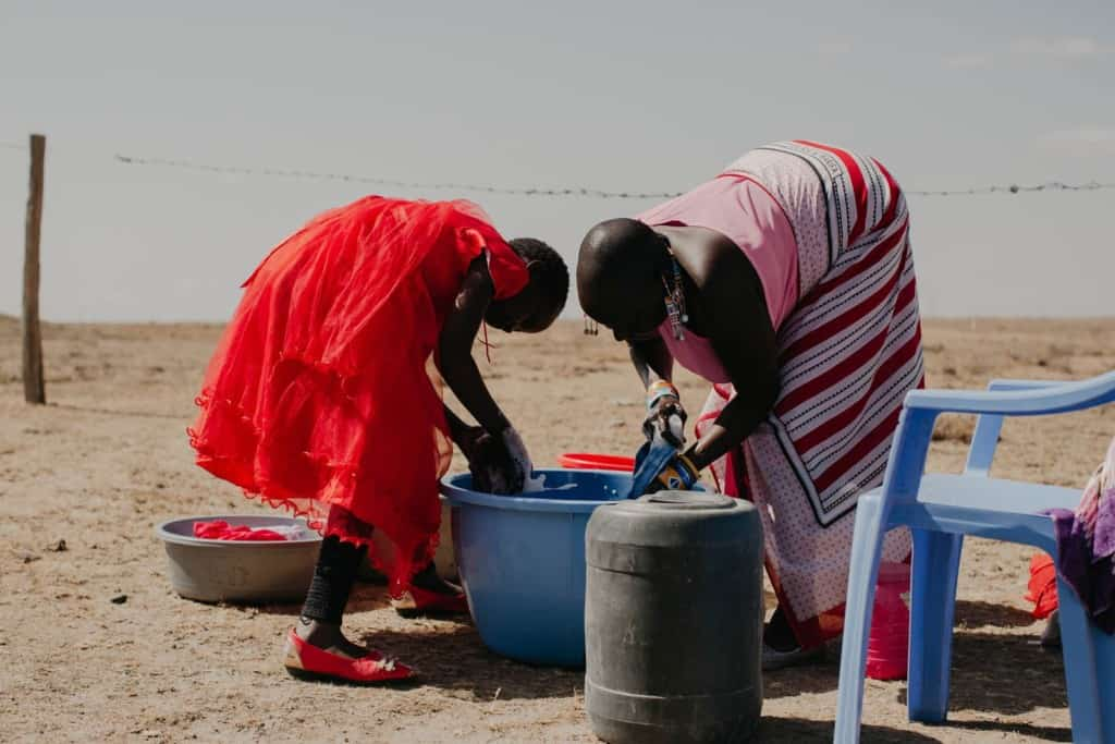 Praise, a 10 year old child, girl, sponsored child, wearing a red dress, bends over to help her mother, parent, adult woman, wash and clean dishes, daily household chores, outside using a large blue tub and soap.