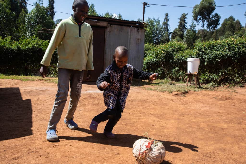 Young boy wearing a black shirt with a geometric pattern on the front and black pants. He is outside his home playing soccer with his older brother who is wearing jeans and a light green shirt.