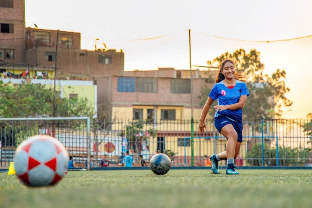 A 15-year-old, adolescent female, teenager, is practicing soccer on a soccer field. She is wearing a blue soccer uniform. Buildings and soccer goals are in the background.