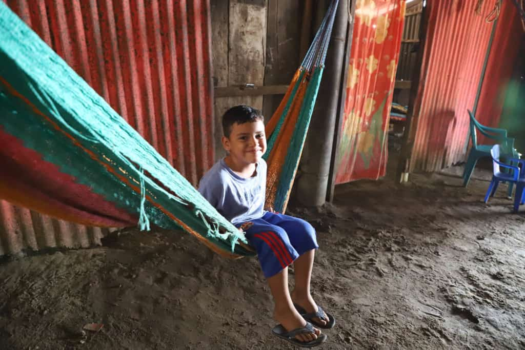Boy sitting in a hammock. The background is the divisions inside the house, and behind them are the bedrooms where the family sleeps.