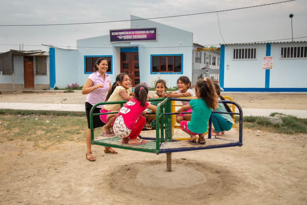 A group of children are playing outside on playground equipment with their tutor Iris Violeta, who is in a lavender shirt. The church building in the background is blue.