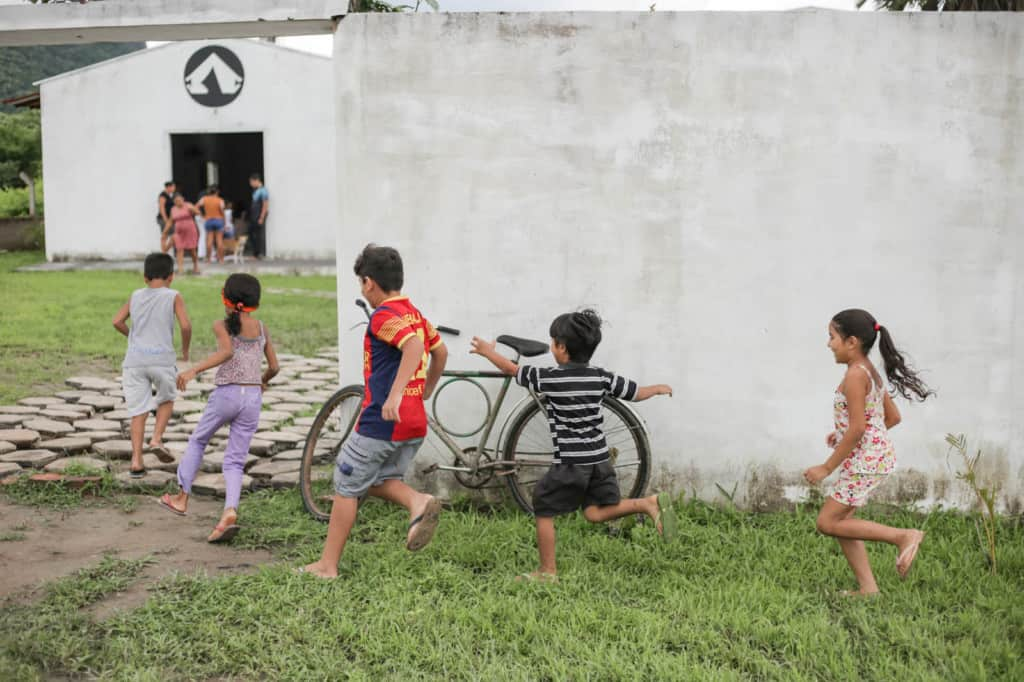A group of children are running through the grass into the child development center, which is in a white building.