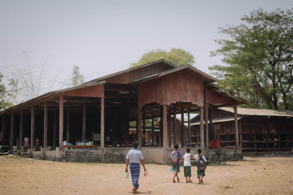 Oosamai is walking behind his children Gungmae-ou (purple shirt) and his twin sons to drop them off at the project center, a large wood structure, building.