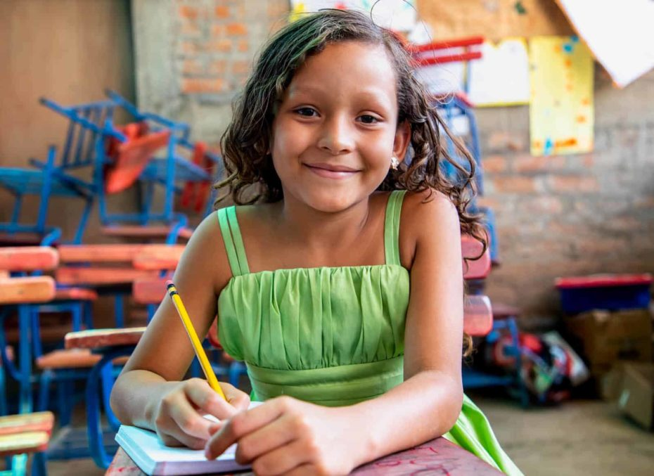 Young girl wearing a green dress and sitting at one of the desks inside one of the newly constructed classrooms. She is holding a pencil in her hand, and there is a notebook on her desk. In the background there are more desks and posters that the children made and hung from the walls.