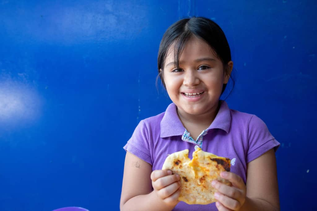A 9 year old girl holds in her hand one 'pupusa' stuffed with cheese and shredded carrot. She smiles joyfully. She is wearing a purple polo shirt and has her hair in a ponytail. The background is a blue wall.