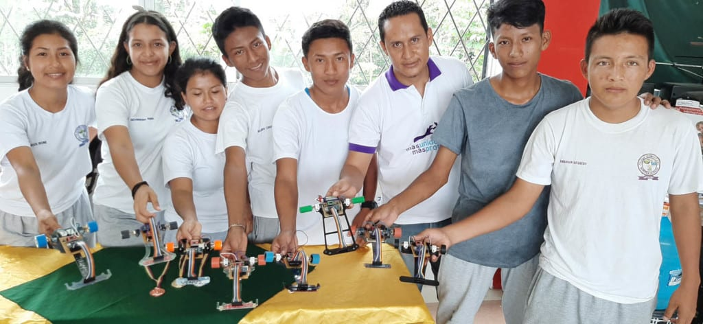 A group of young adults, all wearing white t-shirts, standing together showing their robotics projects.