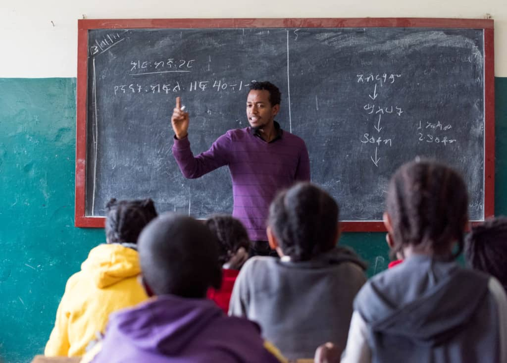 Daniel, wearing a purple sweater, is with a group of children at the Compassion project. The children are sitting at wooden desks and Daniel is standing in the front of the classroom. There is a chalkboard behind him.