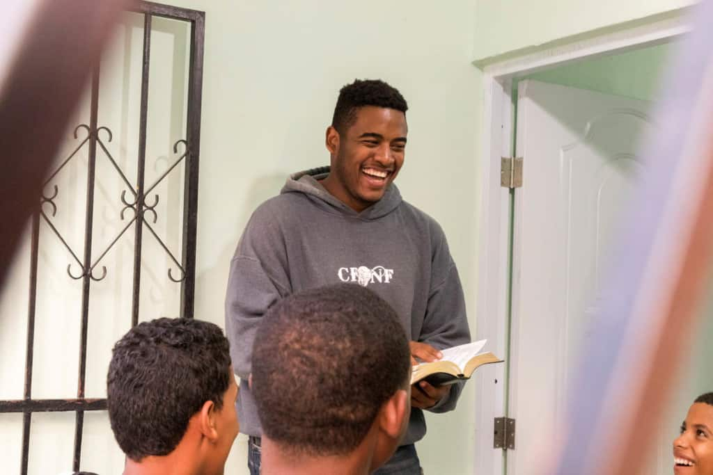 Oscar is inspiring people by speaking about identity to a group of 15-18 years old with his Bible in hand, wearing a gray sweatshirt.