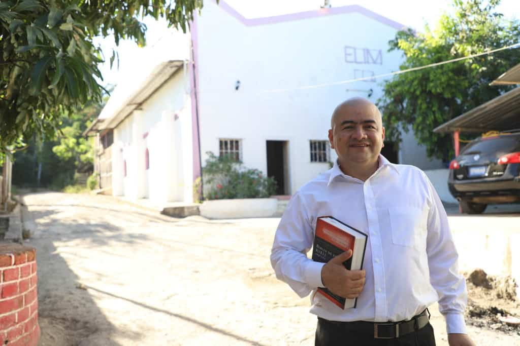 Pastor Pedro Segovia is standing by a dirt alley. He has a Bible in his hand. He is wearing a white button-down shirt and black pants. The background is the Church's temple with the word 'ELIM' which is the name of the evangelical denomination. Pastor Pedro is smiling and making eye contact with the camera.
