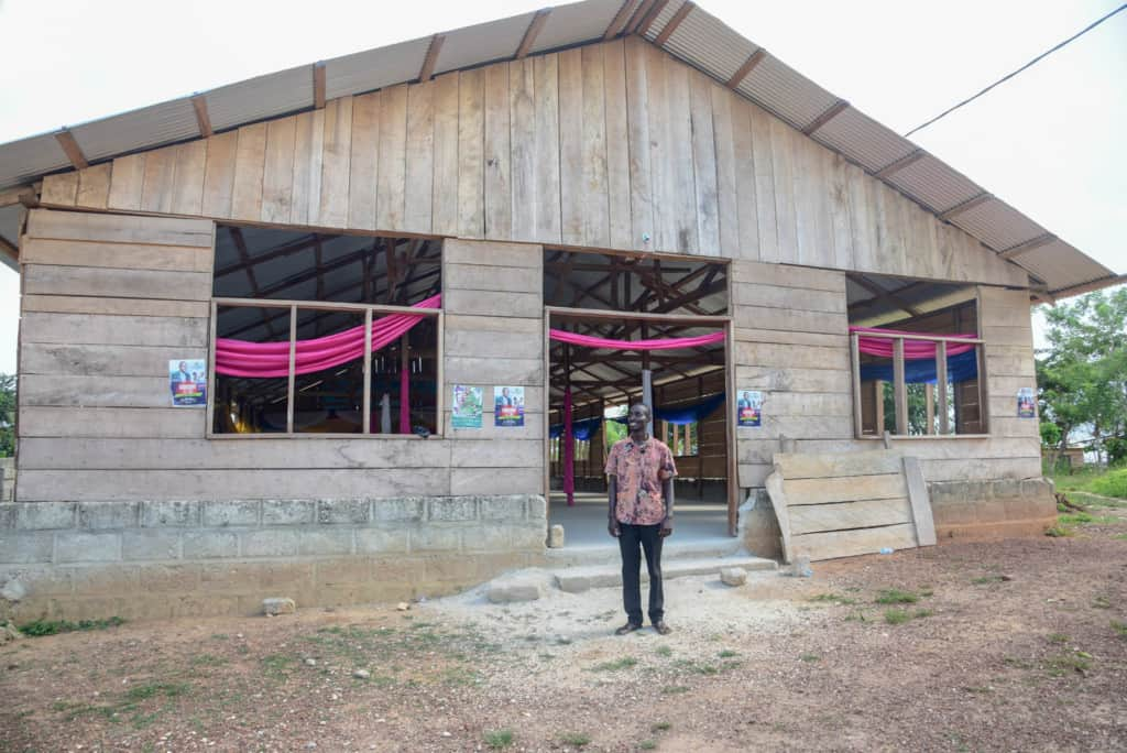 Pastor Joseph is standing in front of a new building in this photo of churches around the world. He is wearing dark pants and a pink patterned shirt.