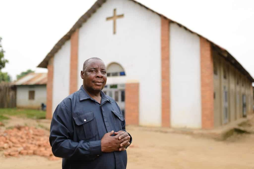 Pastor Monday Justus wearing a black shirt and is standing with his hands laced together in front of the church.