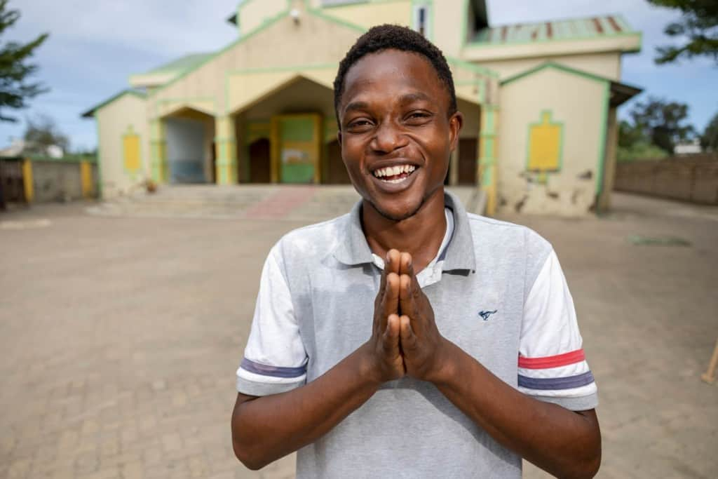 Kelvin is wearing a white shirt and jeans. He is standing outside the Compassion center and church with his hands touching in front of him. The building is yellow and green.