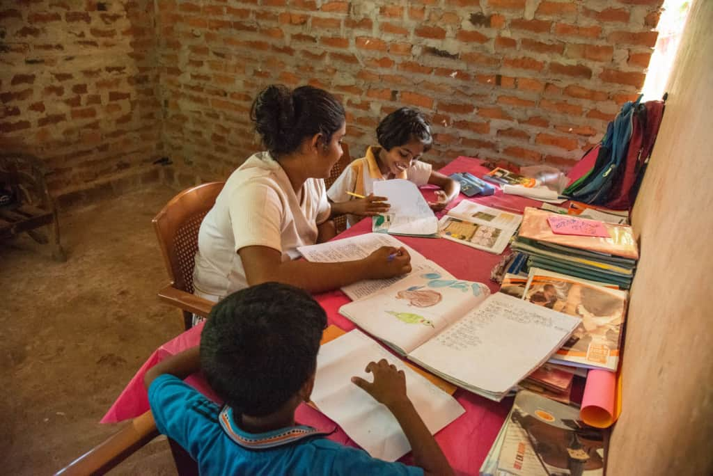 The children are sitting at  a table working on their homework. There are brick walls behind them.