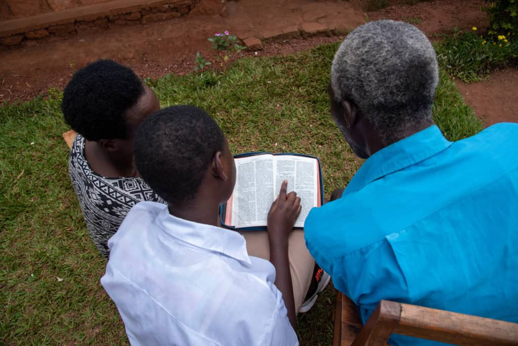 Daughter, father and mother in front of their house reading a Bible.