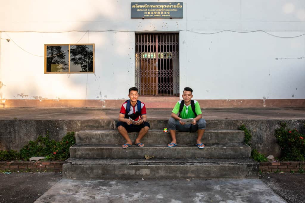 Sirasak and Chaiweera are sitting in front of a white Church building where they both always hang out during a break between Thai school and Chinese school.