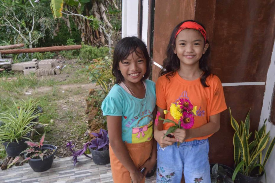Keysha is wearing an orange shirt and light jeans. She is standing outside with her friend and is holding a bouquet of pink and yellow flowers.