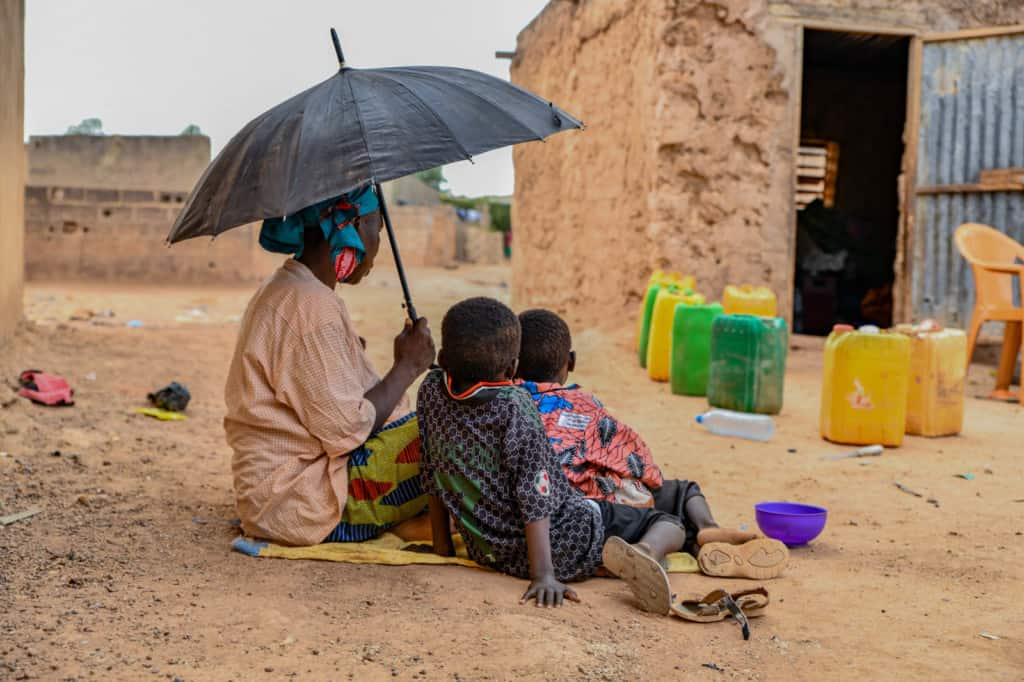 Alima is wearing a pink shirt and a colorfully patterned skirt. She is holding up a black umbrella. Her two grandsons, Fatafou and Kassoum, are sitting with her. In front of their home are plastic chairs and jerry cans.