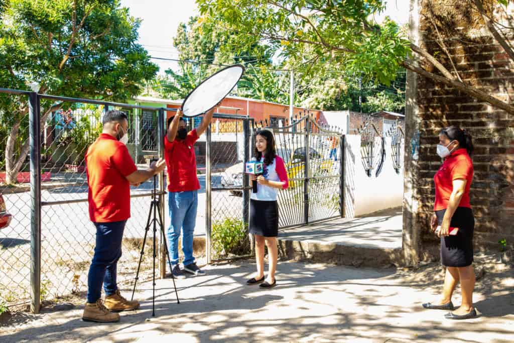Cristina is wearing a white shirt with pink sleeves and a black skirt. She is being recorded with a cell phone in front of her Compassion center, sharing a word of encouragement.