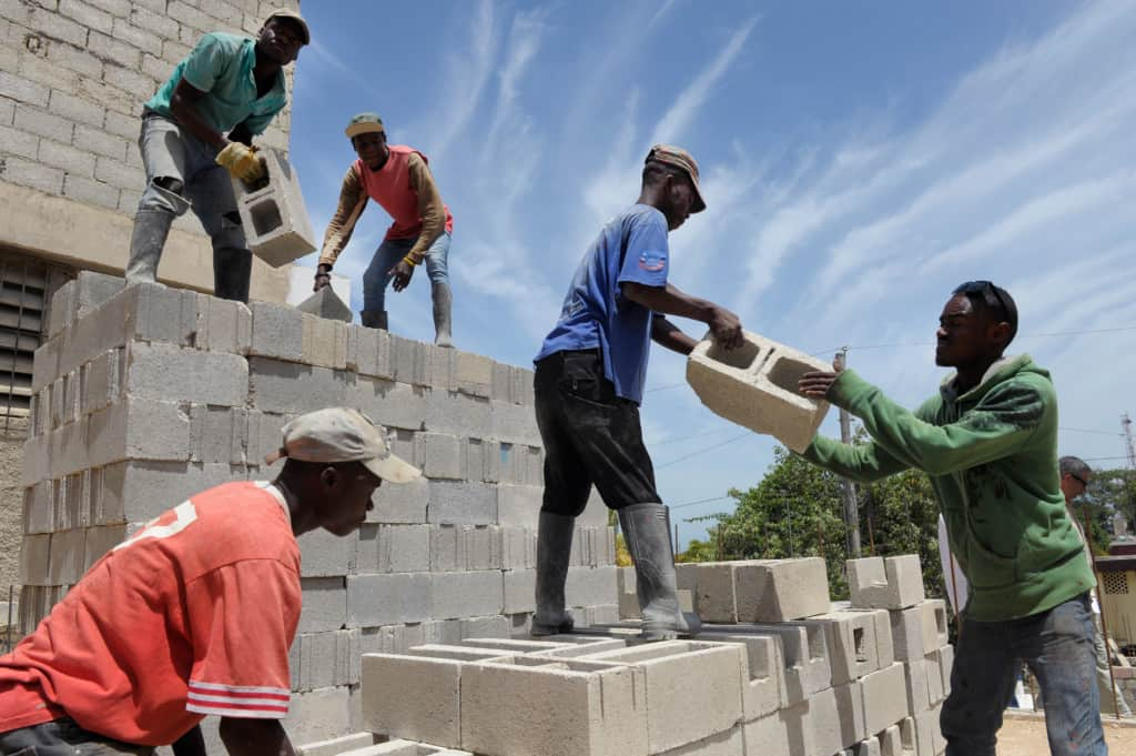 Haitian workers rebuild a school that was destroyed in the 2010 earthquake