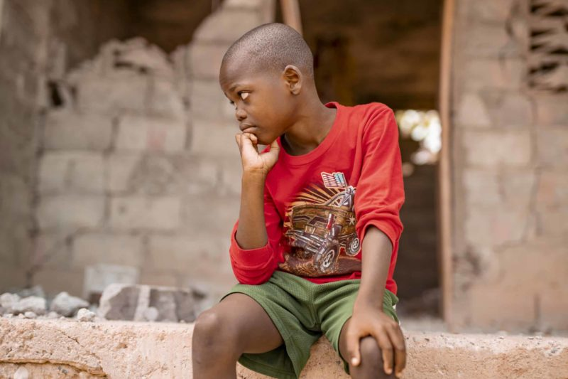 A Haitian boy wearing a red shirt and green shorts has a somber expression. He is sitting in front of a building damaged in a 2018 earthquake in Haiti.