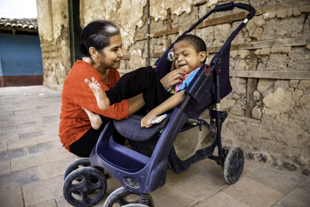 A mother smiles and plays with her son, who is smiling in a wheelchair