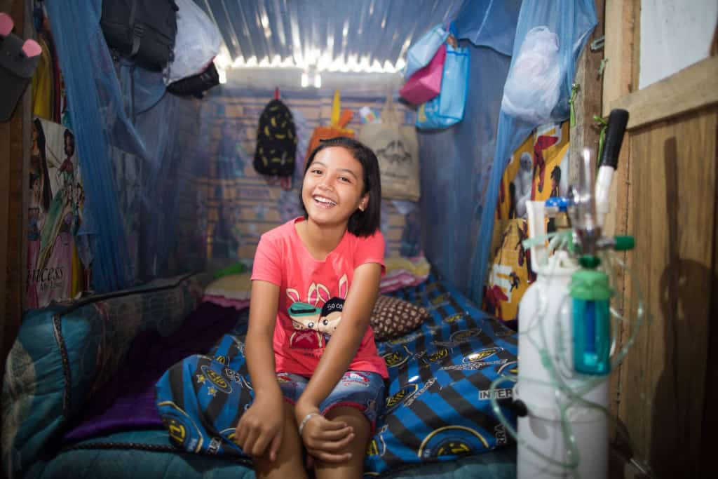 A girl living in poverty with disabilities, sits on her bedroom in her home in Indonesia