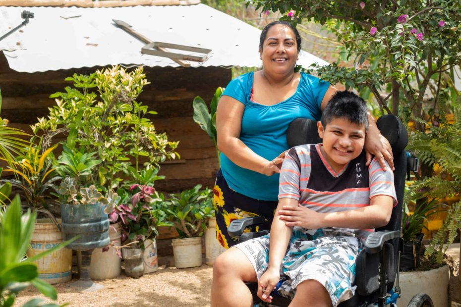 A boy smiles as he sits in a wheelchair. His mother stands behind him with her arms on his shoulders.