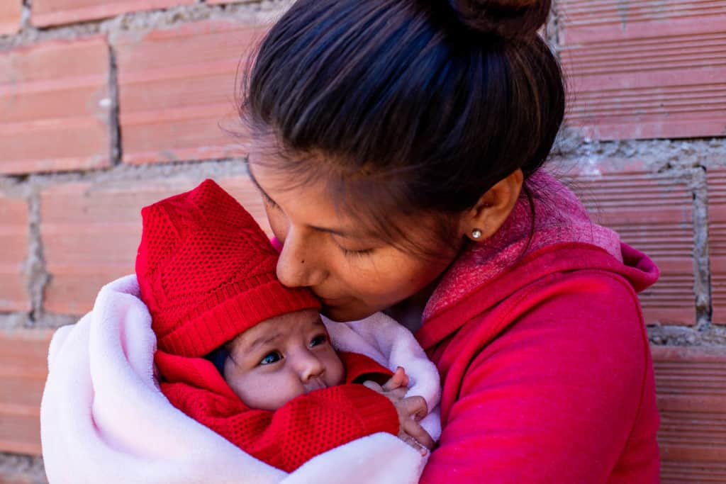 Saida is wearing a red sweatshirt and black leggings. She is holding her baby, Salome, wearing a red outfit and is wrapped in a pink blanket. They are standing in front of a brick wall.