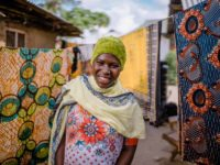 Warda, in a yellow scarf and green hat, is standing in front of laundry hanging on clotheslines outside her home.